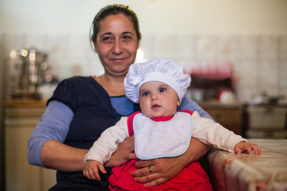 Grandma Ridarova with the child of her son Asan Ridarov and his wife  Radife Ridarova during door to door activity with Romina in the Roma community of Crnik. Asan Ridarov (left) had problems - because of being Roma - leaving Macedonia for  Germany (passport issue).
