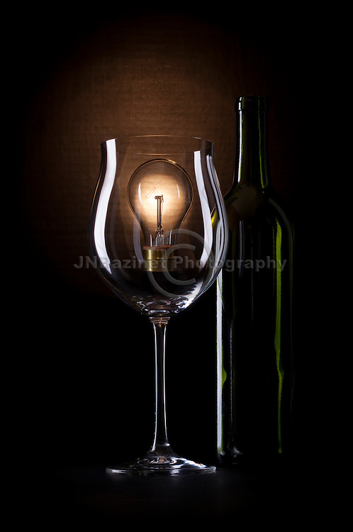 Wine glass and wine bottle silhouette in moody setting with a light bulb representing the complexities of the drink.
