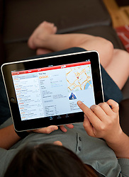 close up of woman using iPad digital tablet computer to check restaurant reviews using Yelp app