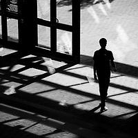 Silhouetted person walking through shadows in an urban environment