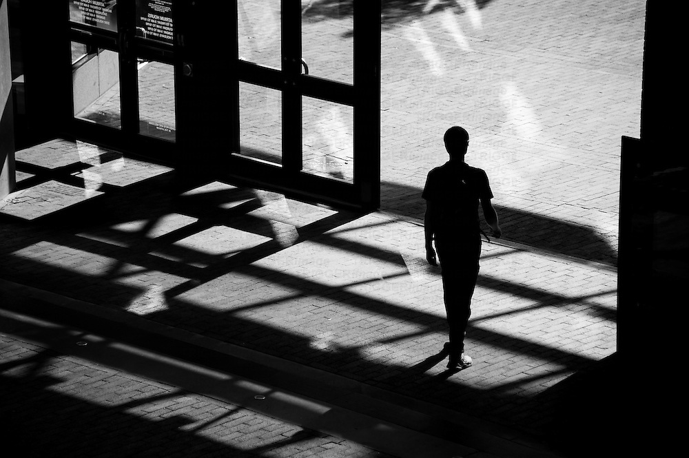 Silhouetted person walking through shadows in an urban environment