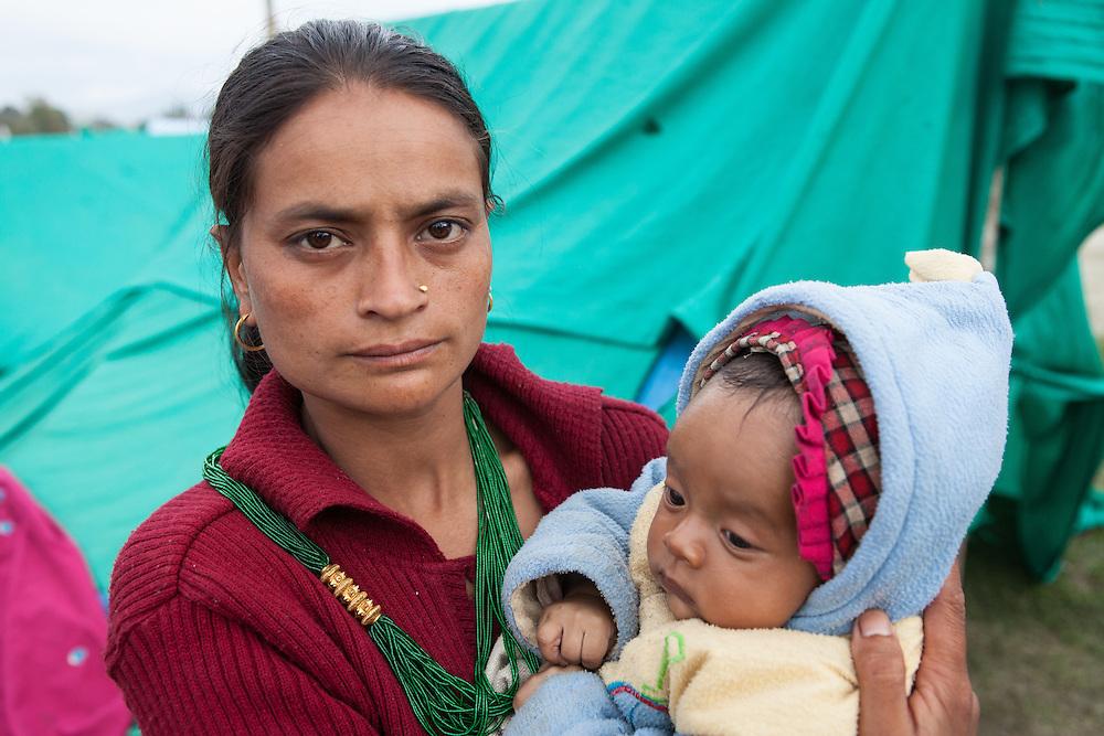 Baby in de armen van haar moeder in een tentenkamp in het centrum van Kathmandu.