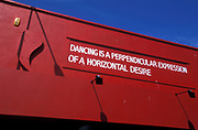 Sign reading 'Dancing is a perpendicular expression of a horizontal desire', 2000's