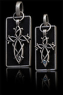 Digital capture of a pair of pewter crosses with semi precious stones on a grafite base.
