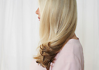 Senior woman in studio profile face obscured by hair