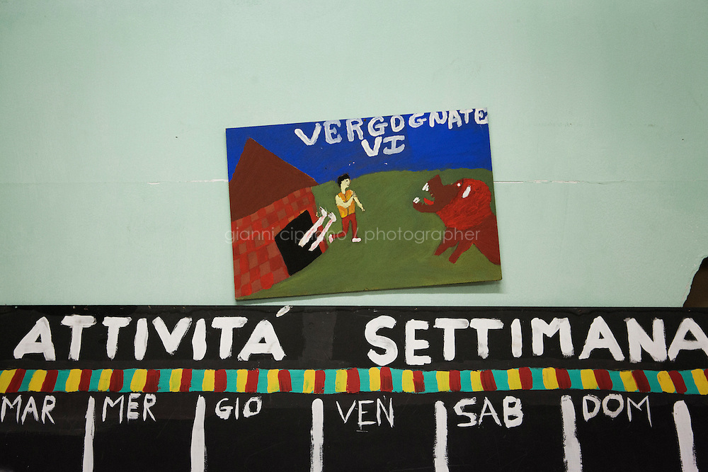 "ROME, ITALY - 25 NOVEMBER 2014: A painting with written ""Shame on you"" made by the  young asylum seekers of the Accommodation Center for Asylum Seekers in Tor Sapienza, a working-class neighborhood in the outskirts of Rome, Italy, on November 25th 2014. Tor Sapienza has seen several days and nights of violence against refugees by residents who blame foreigners for crimes."