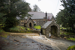 © Licensed to London News Pictures. 21/01/2018. Llandre,  UK. Flood water cascades like a river down the main street in LLANDRE near Aberystwyth in Mid Wales, after hours of torrential rain caused the small steam that runs through he village to dramatically burst its banks . Local residents  made improvised sandbags and barriers to try to divert the water away from their houses. The stream overflowed high above the village just outside the parish church, sending debris down and washing away parts of the road surface .Photo credit: Keith Morris/LNP
