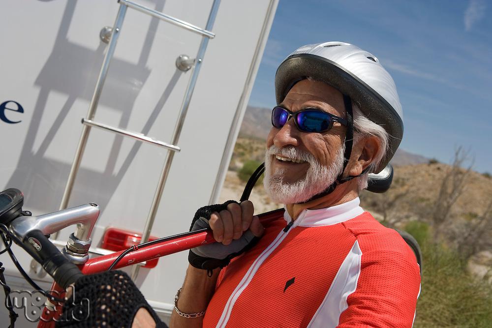 Senior man carrying bike