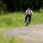 Kid ridding a bicycle in the town of Rincon Santo in the region of Ocu, Province of Herrera, Republic of Panama.  Ocu is an area of the country well known for the fabrication of typical Panamanian dress.