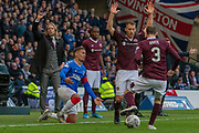 James Tavernier (C) of Rangers FC gets challenged in front of Hearts Interim Manager Austin MacPhee during the Betfred Scottish League Cup semi-final match between Rangers and Heart of Midlothian at Hampden Park, Glasgow, United Kingdom on 3 November 2019.