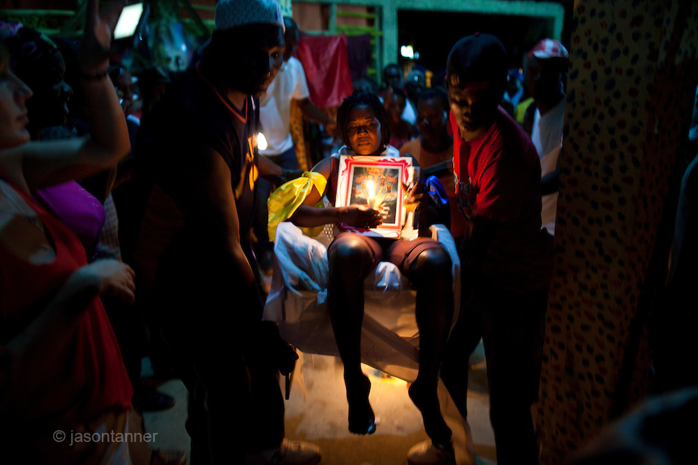 Dominican Republic: A woman undergoes initiation 'in the chair' at the compound of Bleo, a Vodú  priest and head of El GaGá de San Luis on the outskirts of Santo Domingo...Initiating ceremonies and rituals occur 1 week ahead of the main GaGá festivities on Easter weekend. Those initiated, commit to a promise the spirits for 3, 7, 14 or 21 years. If  they fail in their promise then it is said they are cursed for the remainder of the their lives.