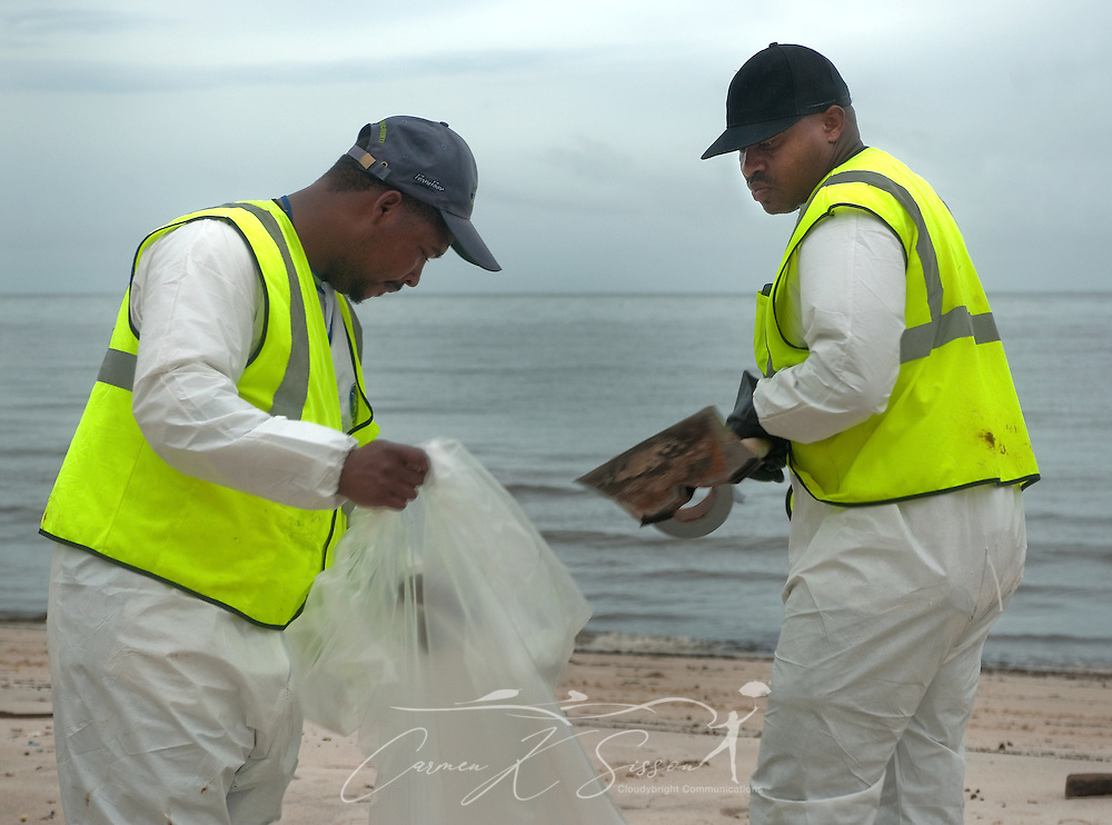 Oil spill cleanup workers remove tar patties from the beach in Gulfport, Miss. June 30, 2010. Mississippi had been largely spared from the effects of the Deepwater Horizon oil rig explosion April 20, 2010, but winds from Hurricane Alex began pushing oil ashore earlier this week, affecting beaches from Biloxi to Pass Christian.(Photo by Carmen K. Sisson/Cloudybright)