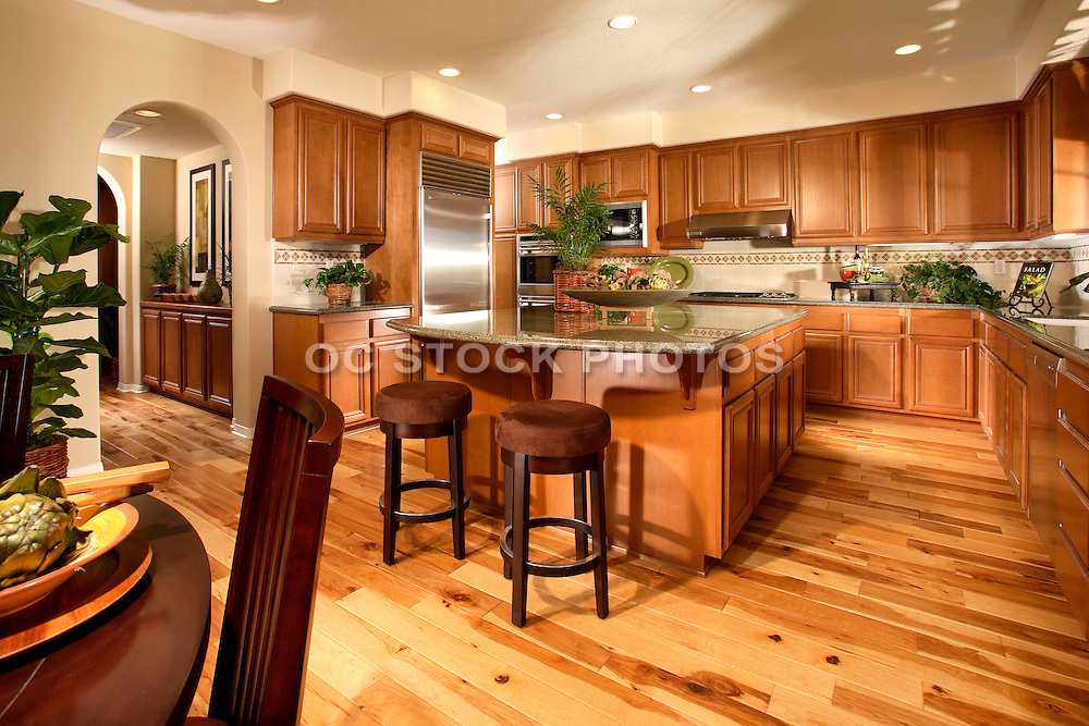 Model Home Large Kitchen With Pine Hard Wood Flooring, Honey Colored Cabinets