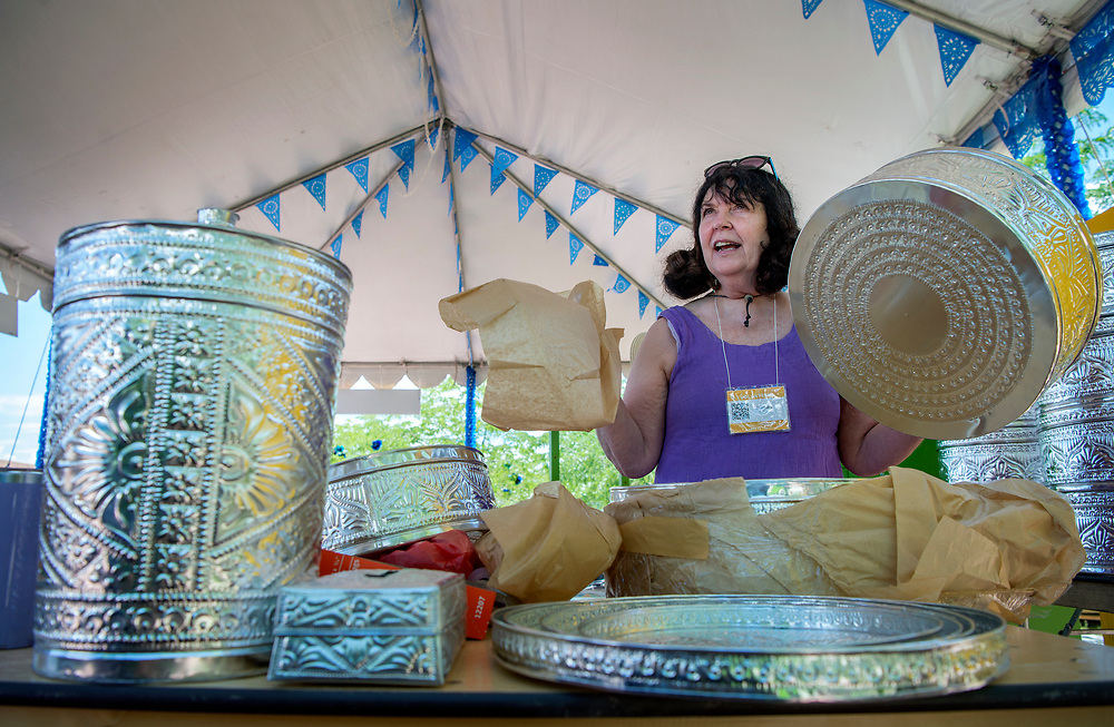 em071217e/b/Rosemary Molnar, from Santa Fe, unwraps hand-made tins from India to be sold in the Ambiance tent at the 2017 International Folf Art Marker on Museum Hill in Santa Fe. She is one of around 2000 volunteers that are helping with the market this year. The Ambiance tent sells items that are used to decorate Museum Hill for the markter and the money raised goes to supporting the International Folk Art Market. The event starts Thursday and runs through the weekend but the main public events are Saturday and Sunday with 160 artist from 53 countries. Photo shot Wednesday July 12, 2017.  (Eddie Moore/Albuquerque Journal)