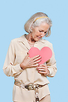 Senior woman in casuals holding red paper heart against blue background