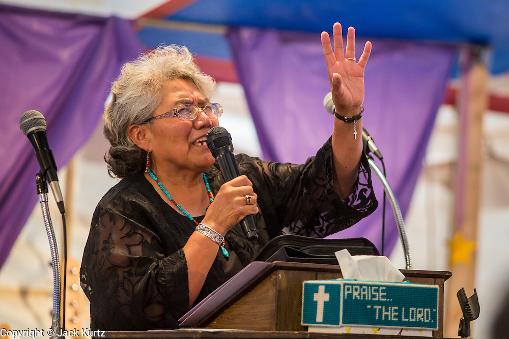"12 JULY 2012 - FT DEFIANCE, AZ:    Sister ARLINDA SCOTT leads a prayer at the 23rd annual Navajo Nation Camp Meeting in Ft. Defiance, north of Window Rock, AZ, on the Navajo reservation. Preachers from across the Navajo Nation, and the western US, come to Navajo Nation Camp Meeting to preach an evangelical form of Christianity. Evangelical Christians make up a growing part of the reservation - there are now more than a hundred camp meetings and tent revivals on the reservation every year. The camp meeting in Ft. Defiance draws nearly 200 people each night of its six day run. Many of the attendees convert to evangelical Christianity from traditional Navajo beliefs, Catholicism or Mormonism. ""Camp meetings"" are a form of Protestant Christian religious services originating in Britain and once common in rural parts of the United States. People would travel a great distance to a particular site to camp out, listen to itinerant preachers, and pray. This suited the rural life, before cars and highways were common, because rural areas often lacked traditional churches.PHOTO BY JACK KURTZ"