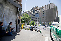 An undercover Iranian policeman (L) holds a weapon outside the Iranian parliament in the capital Tehran on June 7, 2017 during an attack on the complex. The Islamic State group claimed its first attacks in Iran as gunmen and suicide bombers killed at least five people in twin assaults on parliament and the tomb of the country's revolutionary founder in Tehran.PHOTO BY VAHABZADEH FARSNEWS / PARSPIX