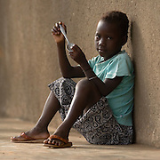 A girl holding a spoon sits outside the Ying Anglican Primary School in the Savelugu-Nanton district, northern Ghana on Monday June 4, 2007. Through a partnership between parents and Christian Relief Services (CRS) children a provided with a meal every day. According to one of the teachers, this alone is responsible for a 40 percent increase in attendance.