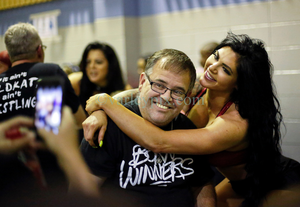 12 March 2016. Metairie, Louisiana.<br /> Wrestling action from Wildkat Sports and Entertainment's 'March into Mayhem' at the Meisler Middle School. Wrestler Katie Forbes poses with a happy fan during the half time break. <br /> Photo&copy;; Charlie Varley/varleypix.com