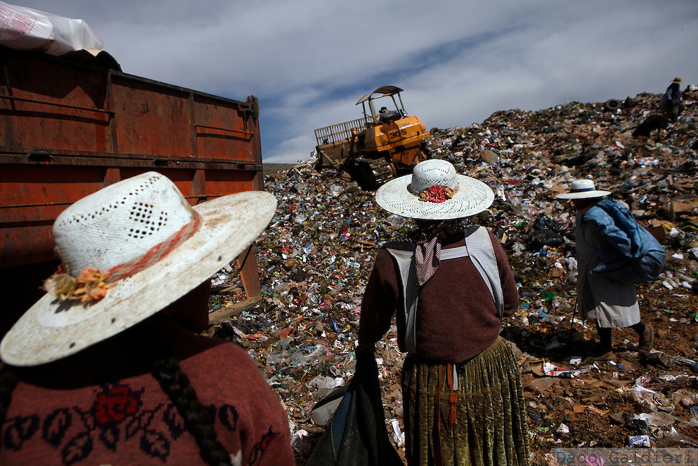 Three Quechua women scavenge the garbage as a caterpillar moves and compacts the trash at  the Kara Kara garbage dump in the outskirts of Cochabamba, Bolivia, Saturday, April 17, 2010. The main dump in the Cochabamba metropolitan area  receives some 400 tons of non recycled garbage each day and faces a mandatory closure next June due to the proximity to inhabited areas.