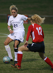 Kelly Hammond (21) challenges a Liberty defender in the first half.  Hammond had a goal and an assist as UVA beat LU 4-0 to advance to the second round of the Women's NCAA Soccer Tournament.