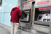 Israel, Tel Aviv, Allenby street, Man withdraws money from an ATM (Automatic Teller Machine)