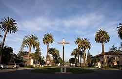 Cross surrounded by palm trees in front of Mission Santa Clara de Asís, Santa Clara University, Santa Clara, California, United States of America.
