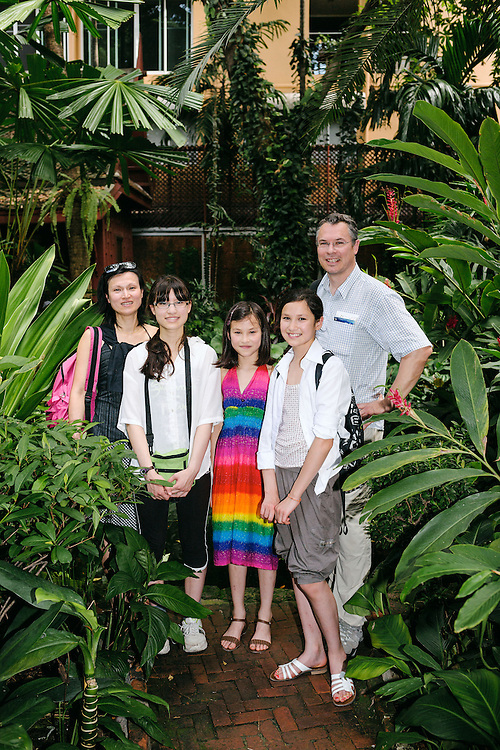 A french family on holiday visiting the Jim Thompson House museum. At the back is father Guillaume and mother Siew Beau. In front from left are the children Lea (13 yrs), Na&euml;l (9 yrs) and Camille (12 yrs).  The Jim Thompson House is a museum in Bangkok. It is a complex of various old Thai structures that the American businessman Jim Thompson collected in from all parts of Thailand in the 1950s and 60s. It is one of the most popular tourist destinations in Thailand.<br /> As Thompson was building his silk company, he also became a major collector of Southeast Asian art, which at the time was not well known internationally. He built a large collection of Buddhist and secular art not only from Thailand but from Burma, Cambodia and Laos, frequently travelling to those countries on buying trips.<br /> In 1958 he began what was to be the pinnacle of his architectural achievement, a new home to showcase his art collection. Formed from parts of six antique Thai houses, his home (completed in 1959) sits on a klong (canal) across from Bangkrua, where his weavers were then located. Most of the 19th-century houses were dismantled and moved from Ayutthaya, but the largest - a weaver's house (now the living room) - came from Bangkuar.