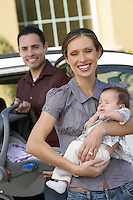 Portrait of woman with baby (1-6 months) by car, man in background