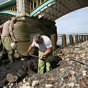 Mudlarkers Andy Johansen and Ian Smith dig holes as they look for items under Southwark Bridge on the bank of the river Thames in London, Britain May 22, 2016. When the river Thames is at low tide, mudlarkers scour the shore for historical artefacts and remains from there City of London's ancient past. Finds can date back to Roman times to when the city was found up until more recent times. Anyone can walk along the river and look for finds, but the uses of metal detectors and digging is restricted. Mudlarkers need to be licences by the Port of London Authority. All find should be register with the Museum of London. REUTERS/Neil Hall