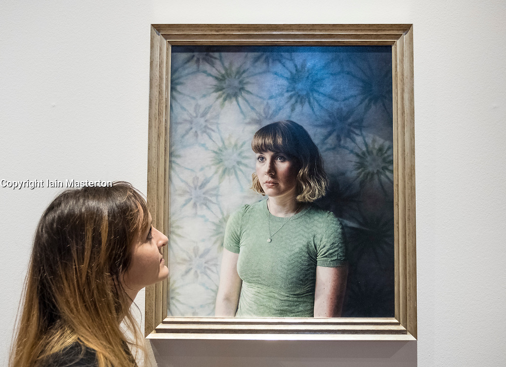 Edinburgh, Scotland, United Kingdom. 14 December, 2017. <br /> Jill Brown, Press and Marketing Officer at National Galleries Scotland looks at painting Jessica by Laura Quinn Harris at the exhibition of BP Portrait Award 2017.<br /> The BP Portrait Award 2017 opens at the Scottish National Portrait Gallery on 16 December 2017.