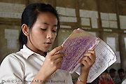 A student reads aloud from her Lao language textbook during a class at Ban Buamlao Primary School in Ban Buamlao, Laos.