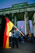 October 3, 1990. Berlin, Germany. Man with German flag standing next to Brandenburg Gate. (Photo Heimo Aga)