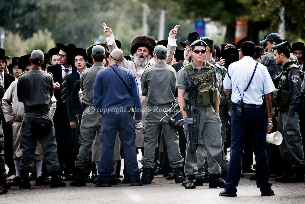 Ultra-orthodox Jewish men protest behind a line of Israeli border policemen outside Intel's office building, in Jerusalem, Saturday, Nov. 28, 2009. Ultra-Orthodox Jews demonstrated outside of Intel's Jerusalem offices on Saturday in order to protest the U.S. company operating on the Jewish Sabbath, which they view as a desecration of the sanctity of the holy city..© ALESSIO ROMENZI