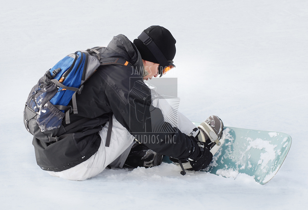 A snowboarder getting ready for the hill.