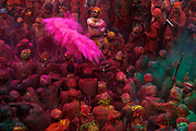 Coloured powders are released over devotees gathered at the Krishna Temple of Shriji, during Lathmar Holi. Men from Barsana raid the town whilst being assaulted with coloured water sprayed from rooftops, they are beaten by Nandgaon's women with large sticks and smeared with Holi coloured powders in a counterpart festival to the one held in Barsana on the previous day. The spectacle is a riot of colour amidst frenzied celebrations.