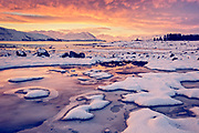 Sunset glow reflects off the frozen winter surface of the banks of Lake Tekapo.