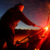 100214  Adron Gardner/Independent<br /> <br /> Embers escape over Gallup firefighter Jimmy silva as he  lights a homecoming bonfire at Miyamura High School in Gallup Thursday.