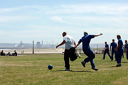 Workers at Seaton Carew near Hartlepool play football on the grass at lunchtime, In distance River Tees estuary & Corus steelworks; Teesside; NE England UK