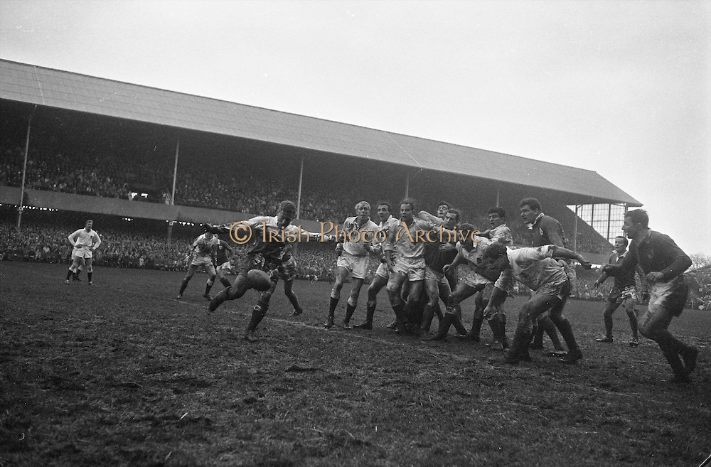 English scrum half, Clarke, kicks to touch while teammates Rogers, Wightman and Dovey hold off Irish,.. Irish Rugby Football Union, Ireland v England, Five Nations, Landsdowne Road, Dublin, Ireland, Saturday 9th February, 1963,.9.2.1963, 2.9.1963,..Referee- H B Laidlaw, Scottish Rugby Union, ..Score- Ireland 0 - 0 England, ..Irish Team, ..B D E Marshall, Wearing number 15 Irish jersey, Full Back, Queens University Rugby Football Club, Belfast, Northern Ireland,..W R Hunter, Wearing number 14 Irish jersey, Right Wing, C I Y M S Rugby Football Club, Belfast, Northern Ireland, ..J C Walsh,  Wearing number 13 Irish jersey, Right Centre, University college Cork Football Club, Cork, Ireland,..P J Casey, Wearing number 12 Irish jersey, Left Centre, University College Dublin Rugby Football Club, Dublin, Ireland, ..N H Brophy, Wearing number 11 Irish jersey, Left wing, Blackrock College Rugby Football Club, Dublin, Ireland, ..M A English, Wearing number 10 Irish jersey, Stand Off, Landsdowne Rugby Football Club, Dublin, Ireland, ..J C Kelly, Wearing number 9 Irish jersey, Scrum Half, University College Dublin Rugby Football Club, Dublin, Ireland,..R J McLoughlin, Wearing number 1 Irish jersey, Forward, Blackrock College Rugby Football Club, Dublin, Ireland, ..A R Dawson, Wearing number 2 Irish jersey, Forward, Wanderers Rugby Football Club, Dublin, Ireland, ..S Millar, Wearing number 3 Irish jersey, Forward, Ballymena Rugby Football Club, Antrim, Northern Ireland,..W A Mulcahy, Wearing number 5 Irish jersey, Captain of the Irish team, Forward, Bective Rangers Rugby Football Club, Dublin, Ireland,  ..W J McBride, Wearing number 5 Irish jersey, Forward, Ballymena Rugby Football Club, Antrim, Northern Ireland,..E P McGuire, Wearing number 6 Irish jersey, Forward, University college Galway Football Club, Galway, Ireland,..C J Dick, Wearing number 8 Irish jersey, Forward, Ballymena Rugby Football Club, Antrim, Northern Ireland,..M D Kiely, Wearing number 7 Irish jersey, Forward,