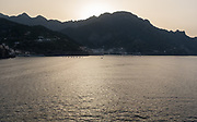 Morning sun casts golden light across the mountains and sea along the Amalfi Coast in Italy