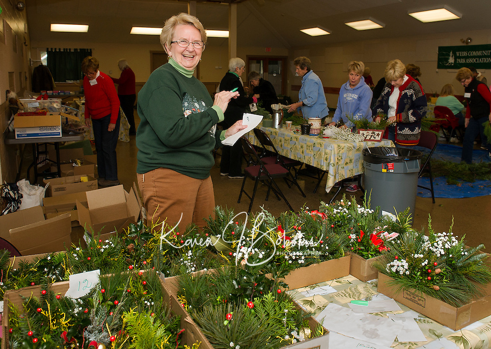 Marge Dyer of the Opechee Garden Club checks the final tally on approximately 90 floral arrangements made by members for a special delivery to the Belknap County Nursing Home on Tuesday afternoon.  (Karen Bobotas/for the Laconia Daily Sun)