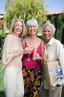 Senior woman with two friends, smiling and holding champagne