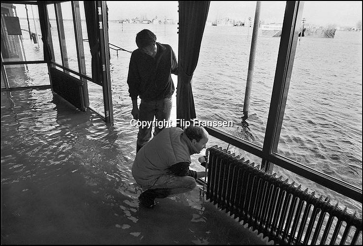 Nederland, Nijmegen 1-2-1995Tijdens historische hoge waterstand van de Waal probeert personeel van een cafe aan de Waalkade het interieur te redden. Hoogwater, milieu, klimaatverandering,overstromen,overstromingschade. Wateroverlast. februari 1995Eind januari, begin februari 1995 steeg het water van de Rijn, Maas en Waal tot record hoogte van 16,64 m. bij Lobith. Een evacuatie van 250.000 mensen was noodzakelijk vanwege het gevaar voor dijkdoorbraak en overstroming. op verschillende zwakke punten werd geprobeerd de dijken te versterken met zandzakken.Late January, early February 1995 increased the water of the Rhine, Maas and Waal to a record high of 16.64 meters at Lobith. An evacuation of 250,000 people was needed because of flood risk. At several points people tried to reinforce the dikes with sandbags.Foto: Flip Franssen/Hollandse Hoogte