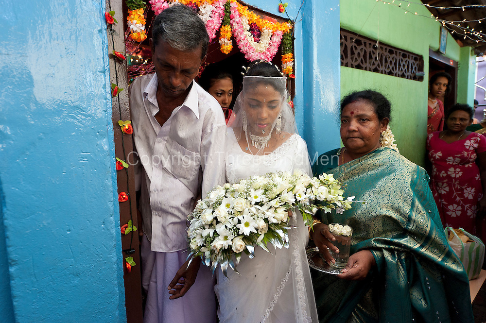 The bride, accompanied by her parents,  leaves her home for a church wedding.