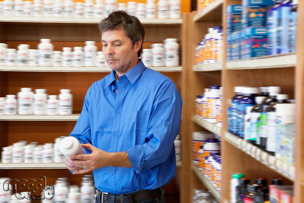 Mature man looking at pill bottle in drugstore