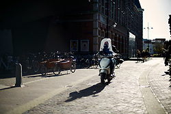 A young man rides his scouter near the theater district. While backlit by the sun his face is lit by reflecting light from the facade of one of the theaters.<br /> <br /> After living abroad for more than three years I visited my old home town. Wondering what has changed I packed both my curiosity and a camera. (Original posted as part of a photo essay 'Revisiting Familiar Grounds' here: http://www.basslabbers.com/WP/?p=1320)