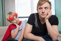 Portrait of sad boy dressed in superhero costume sitting with father on sofa bed at home