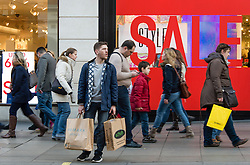 © Licensed to London News Pictures. 20/12/2014. London, UK. Christmas shoppers on London's Oxford Street on the last saturday before Christmas walk past shop  storefronts displaying sales discounts. Photo credit : Richard Isaac/LNP