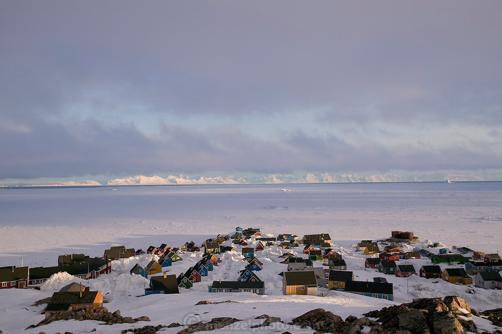 The remote village of Ittoqqortoormiit (population 550), Greenland, catches the late-night sunlight. During the summer here, the sun never actually disappears below the horizon, though it does dip briefly behind the high hills that surround the village. (Supporting image from the project Hungry Planet: What the World Eats.)